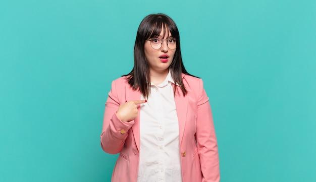 Młoda biznesowa kobieta wygląda na zszokowaną i zaskoczoną z szeroko otwartymi ustami, wskazując na siebie