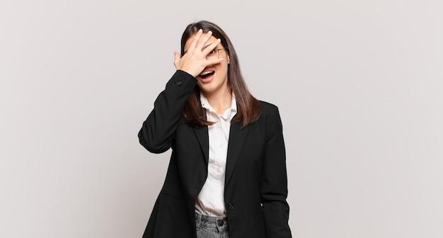 Młoda biznesowa kobieta wygląda na zszokowaną, przestraszoną lub przerażoną, zakrywa twarz dłonią i zerka między palcami