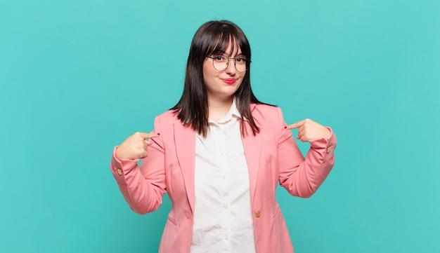 Młoda biznesowa kobieta wyglądająca dumnie, pozytywnie i swobodnie, wskazując na klatkę piersiową obiema rękami