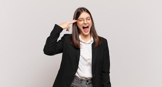 Młoda biznesowa kobieta wyglądająca na niezadowoloną i zestresowaną, samobójczy gest wykonujący znak pistoletu ręką, wskazujący na głowę