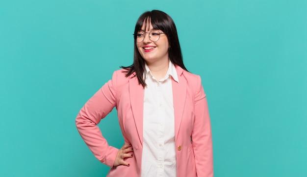 Młoda biznesowa kobieta wyglądająca na szczęśliwą, pogodną i pewną siebie, uśmiechającą się dumnie i patrzącą na bok z obiema rękami na biodrach