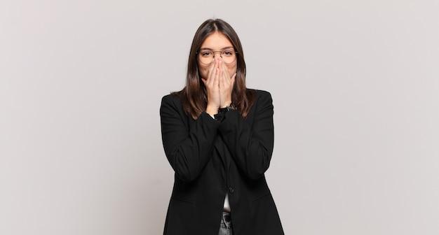 Młoda biznesowa kobieta wyglądająca na szczęśliwą, wesołą, szczęśliwą i zdziwioną zakrywającą usta obiema rękami