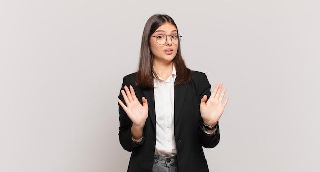 Młoda biznesowa kobieta wyglądająca na zdenerwowaną, niespokojną i zaniepokojoną, mówiącą, że nie moja wina lub ja tego nie zrobiłem
