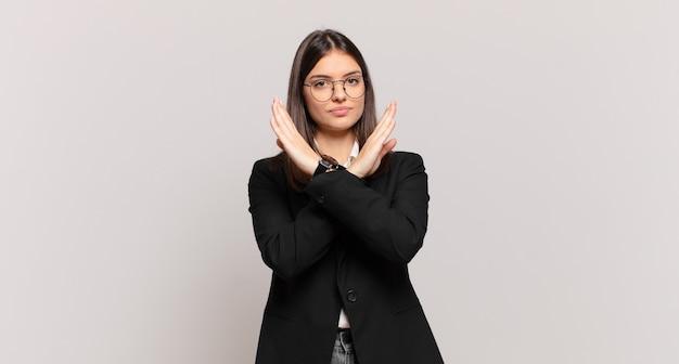 Młoda biznesowa kobieta wyglądająca na zirytowaną i zmęczoną twoją postawą, mówiącą dość! ręce skrzyżowane z przodu, mówiące, żebyś przestała