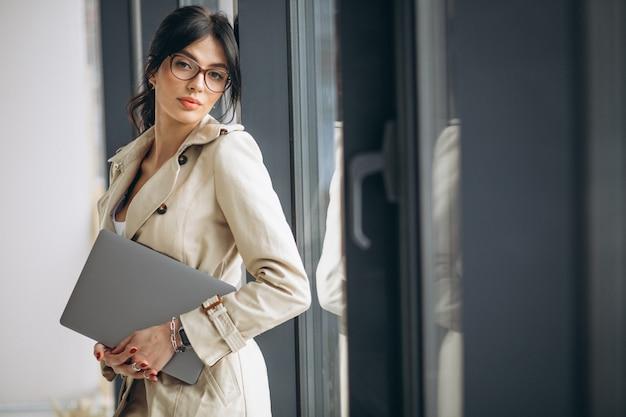 Młoda biznesowa kobieta z laptop pozycją okno w biurze