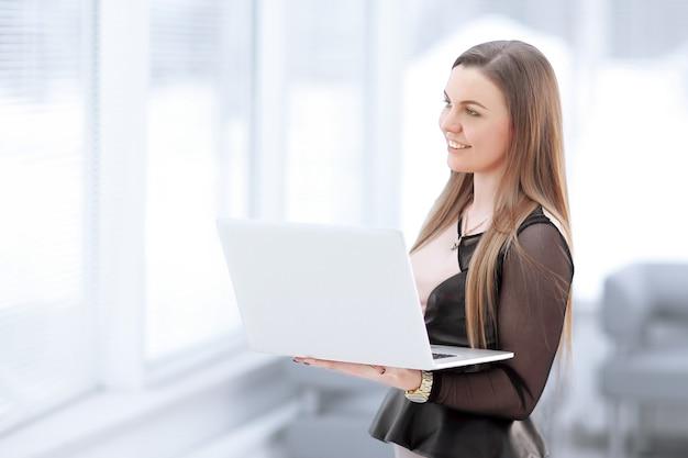 Młoda biznesowa kobieta z laptopa stojącego w holu urzędu