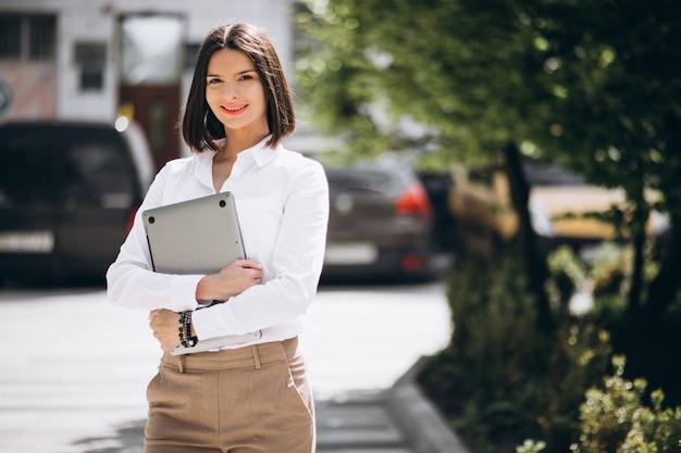 Młoda biznesowa kobieta z laptopem na zewnątrz ulicy