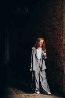 Młoda biznesowa kobieta z rudymi włosami przy użyciu telefonu
