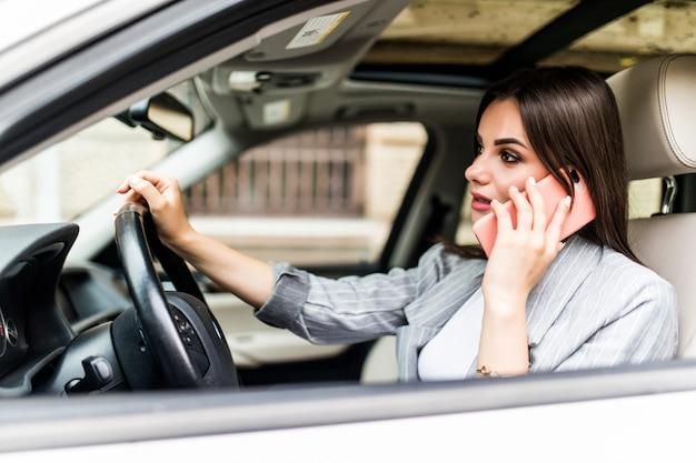 Młoda biznesowa kobieta za pomocą swojego telefonu podczas prowadzenia samochodu