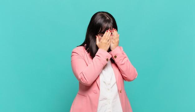 Młoda biznesowa kobieta zakrywająca oczy rękami ze smutnym, sfrustrowanym wyrazem rozpaczy, płaczu, widoku z boku