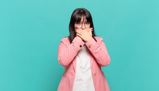 """Młoda biznesowa kobieta zakrywająca usta dłońmi ze zszokowanym, zdziwionym wyrazem twarzy, zachowująca tajemnicę lub mówiąca """"ups"""""""