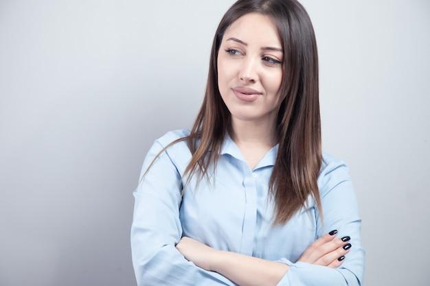 Młoda biznesowa kobieta ze skrzyżowanymi rękami.