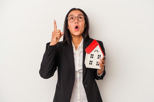 Młoda biznesowa łacińska kobieta trzyma zabawkarski dom odizolowywający na białym tle wskazuje do góry z otwartymi ustami.