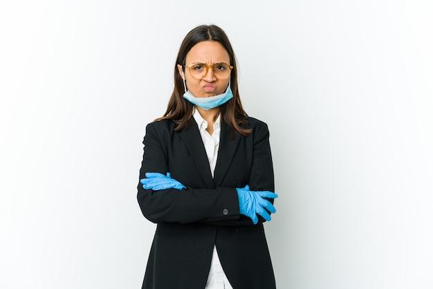 Młoda biznesowa latynoska kobieta ubrana w maskę do ochrony przed covid na białej ścianie marszcząca brwi z niezadowoleniem, trzyma założone ręce.
