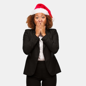 Młoda biznesowa murzynka jest ubranym chirstmas santa kapelusz bardzo okaleczającego i przestraszonego chowanego