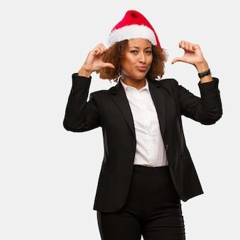 Młoda biznesowa murzynka jest ubranym chirstmas santa kapelusz wskazuje palce, przykład podążać
