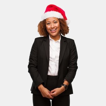 Młoda biznesowa murzynka jest ubranym chirstmas santa kapeluszowego rozochoconego z dużym uśmiechem