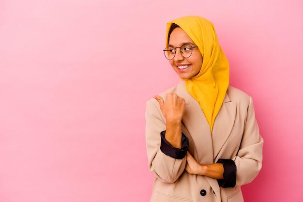 Młoda biznesowa muzułmańska kobieta na białym tle na różowym tle wskazuje palcem kciuka, śmiejąc się i beztrosko.