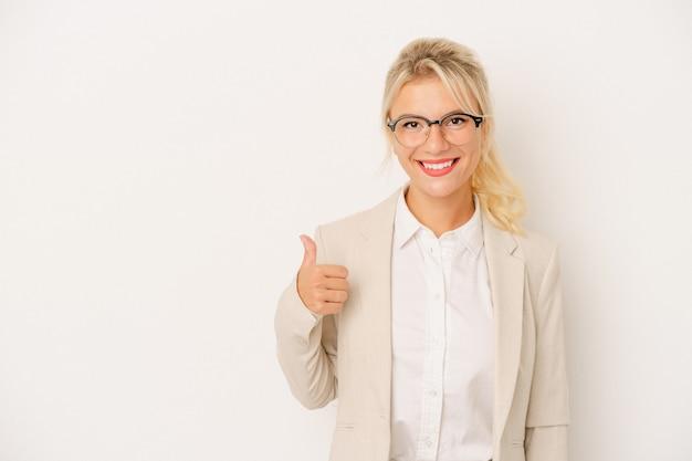 Młoda biznesowa rosjanka na białym tle uśmiecha się i podnosi kciuk w górę