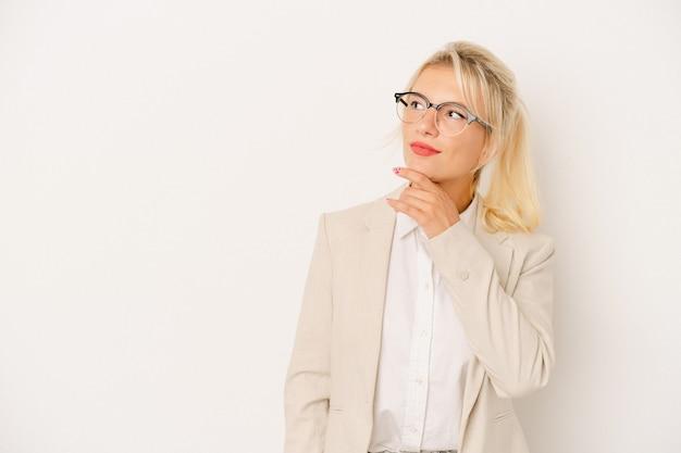 Młoda biznesowa rosyjska kobieta odizolowywająca na białym tle patrzeje z ukosa z wątpliwym i sceptycznym wyrazem.