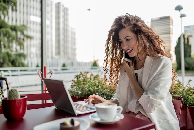 Młoda biznesowa rudzielec kobieta na telefonie komórkowym i komputerze