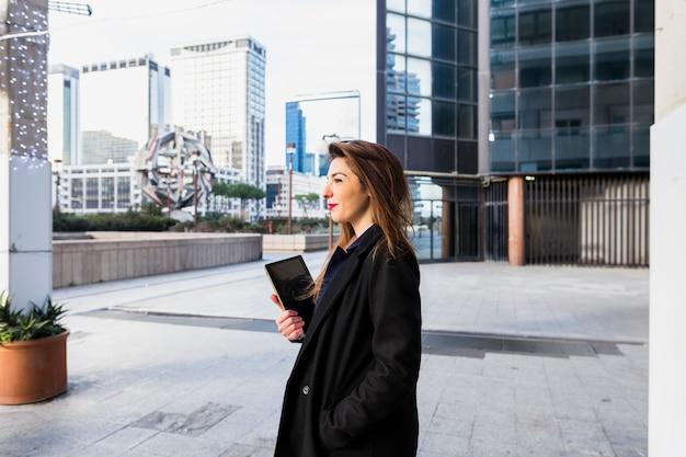 Młoda biznesowej kobiety pozycja z pastylką outside