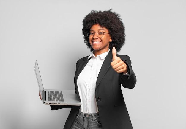 Młoda bizneswoman afro czuje się dumna, beztroska, pewna siebie i szczęśliwa, uśmiecha się pozytywnie z kciukami do góry. pomysł na biznes