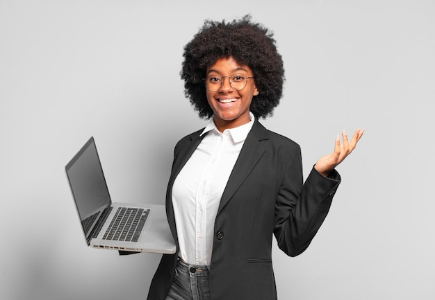 Młoda bizneswoman afro czuje się szczęśliwa, zdziwiona i wesoła, uśmiecha się pozytywnie, realizuje rozwiązanie lub pomysł. pomysł na biznes