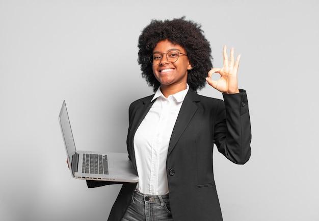 Młoda bizneswoman afro czuje się szczęśliwa, zrelaksowana i usatysfakcjonowana, pokazując aprobatę w porządku gestem, uśmiechając się