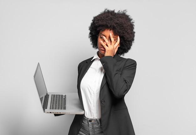 Młoda bizneswoman afro czuje się znudzona, sfrustrowana i senna po męczącej pracy