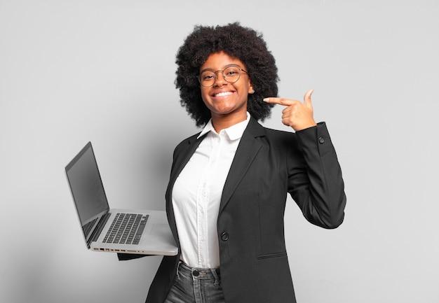 Młoda bizneswoman afro uśmiecha się pewnie, wskazując na własny szeroki uśmiech, pozytywne, zrelaksowane, zadowolone nastawienie. pomysł na biznes