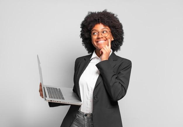 Młoda bizneswoman afro uśmiecha się radośnie i marzy lub wątpi, patrząc w bok. pomysł na biznes