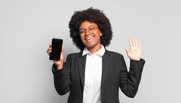 Młoda bizneswoman afro uśmiecha się radośnie i wesoło, macha ręką, wita i wita lub żegna się. pomysł na biznes