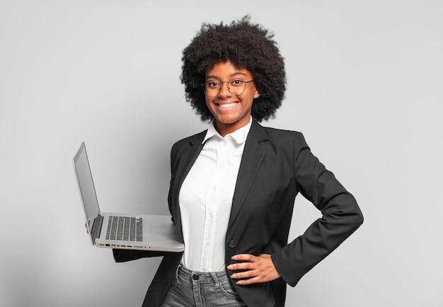 Młoda bizneswoman afro uśmiechnięta radośnie z ręką na biodrze i pewną siebie, pozytywną, dumną i przyjazną postawą. pomysł na biznes