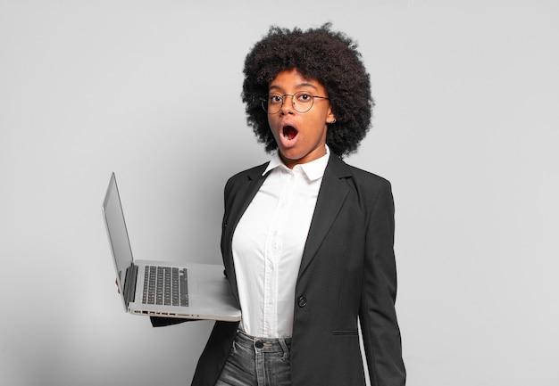 Młoda bizneswoman afro wyglądająca na bardzo zszokowaną lub zaskoczoną, patrząc z otwartymi ustami i mówiącą wow.