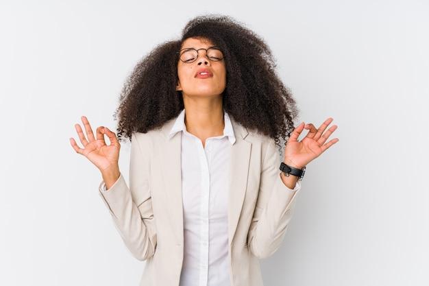 Młoda bizneswoman afroamerykanów relaksuje się po ciężkim dniu pracy, wykonuje jogę.