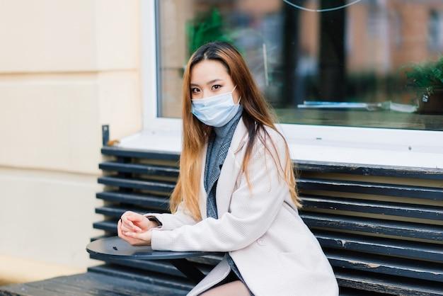 Młoda bizneswoman azjatyckich z maską przy użyciu telefonu i siedząc z odległością poza kawiarnią