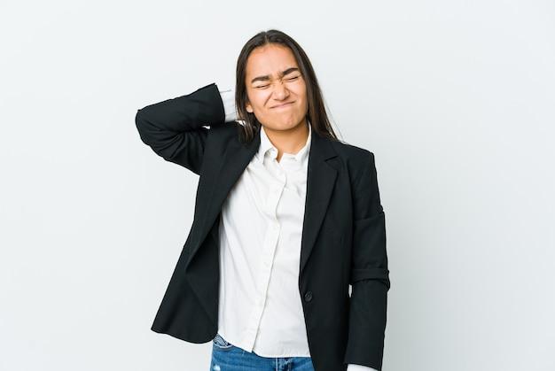 Młoda bizneswoman azjatyckiego na białej ścianie cierpi na ból szyi z powodu siedzącego trybu życia.