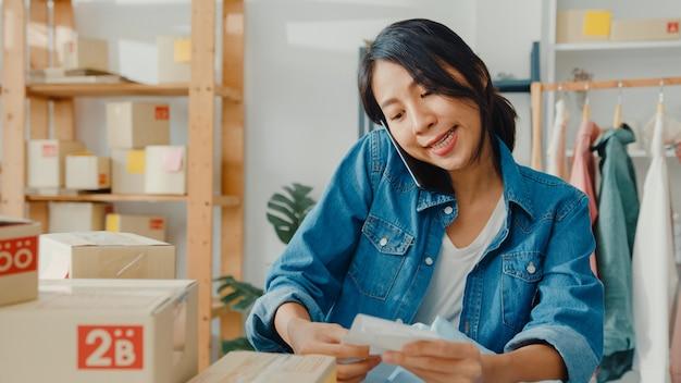 Młoda bizneswoman azjatyckiego za pomocą smartfona odbieranie zamówienia zakupu i sprawdzanie towaru na stanie w biurze domowym