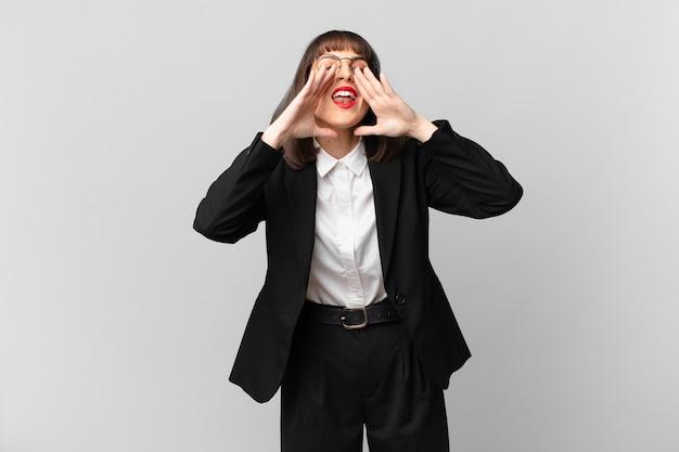 Młoda bizneswoman czuje się szczęśliwa, podekscytowana i pozytywna, wydając wielki okrzyk z rękami przy ustach, wołając