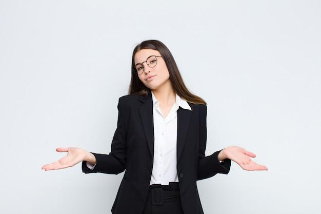 Młoda bizneswoman czuje się zdziwiona i zdezorientowana, niepewna prawidłowej odpowiedzi lub decyzji, próbując dokonać wyboru ponad białą ścianą