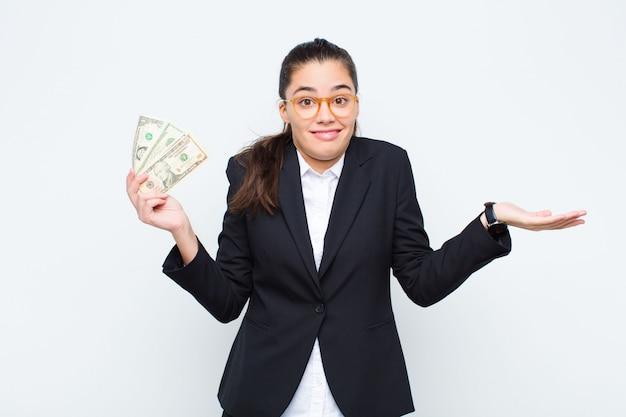 Młoda bizneswoman czuje się zdziwiona i zdezorientowana, wątpi, rozważa lub wybiera różne opcje z zabawnym wyrazem twarzy z banknotami z rachunkami