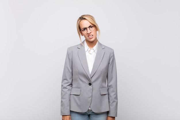 Młoda bizneswoman czuje się zdziwiona i zdezorientowana, z głupim, oszołomionym wyrazem twarzy, patrząc na coś nieoczekiwanego