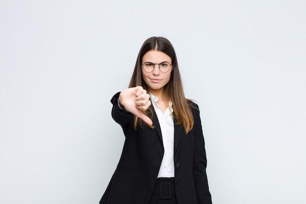 Młoda bizneswoman czuje się zła, zła, zirytowana, rozczarowana lub niezadowolona, pokazując kciuki w dół z poważnym spojrzeniem na białej ścianie