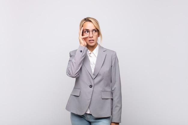 Młoda bizneswoman czuje się znudzona, sfrustrowana i senna po męczącym, nudnym i żmudnym zadaniu, trzymając twarz ręką