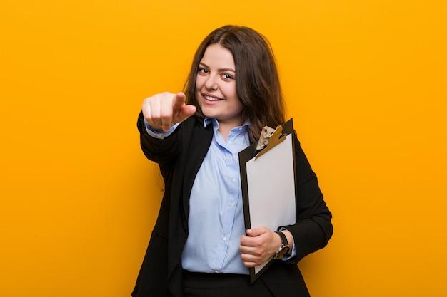 Młoda bizneswoman gospodarstwa schowka wesoły uśmiecha się do przodu