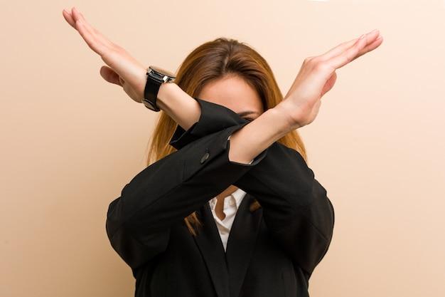 Młoda bizneswoman kaukaski trzymając skrzyżowane ręce, koncepcja odmowy.
