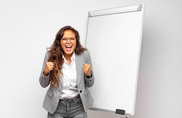 Młoda bizneswoman krzyczy agresywnie z gniewnym wyrazem twarzy lub z zaciśniętymi pięściami świętuje sukces