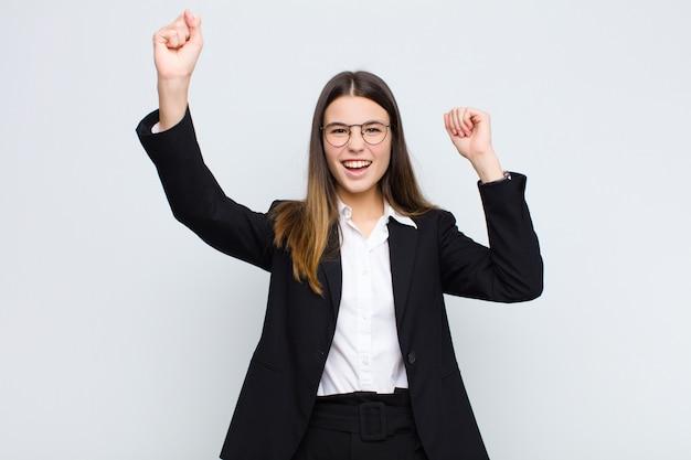 Młoda bizneswoman krzyczy triumfalnie, wyglądając jak podekscytowany, szczęśliwy i zaskoczony zwycięzca, świętujący na białej ścianie
