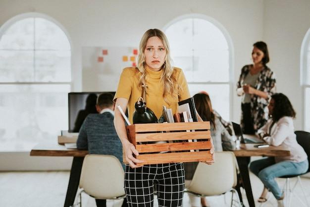 Młoda bizneswoman niosąca drewniane pudełko